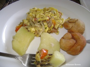 Ackee and saltfish served with boiled yellow yam and johnny cakes (fried dumplings)